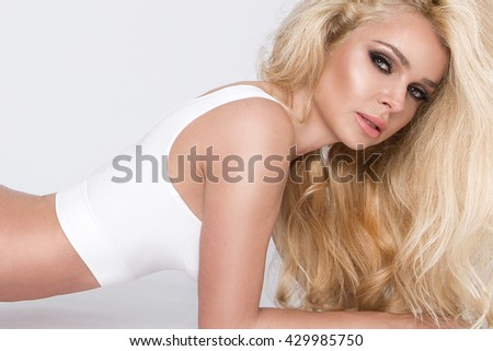 beautiful long-haired blonde slim blonde with perfect face lies on a white background in underwear slimming and sensually looks into the lens