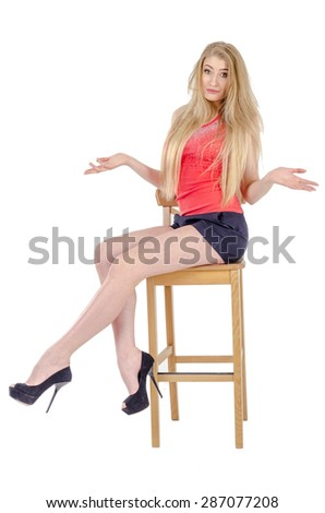 Beautiful long-haired cheerful girl in a short skirt sitting on a chair and gesturing
