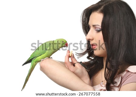 beautiful long-haired girl feeds a green parrot - stock photo
