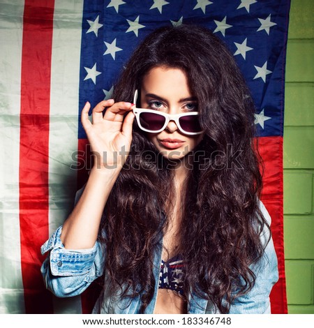 beautiful long haired girl in sunglasses against usa flag poses for the camera - stock photo