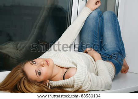 Beautiful long-haired girl, sitting on a window-sill