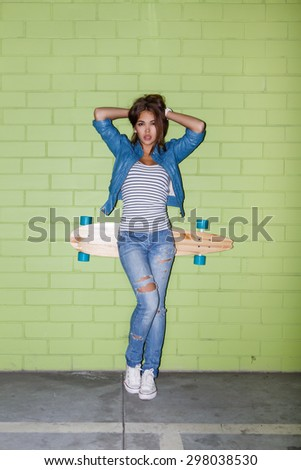 beautiful long-haired woman with wooden skateboard corrects her hairs near the green brick wall