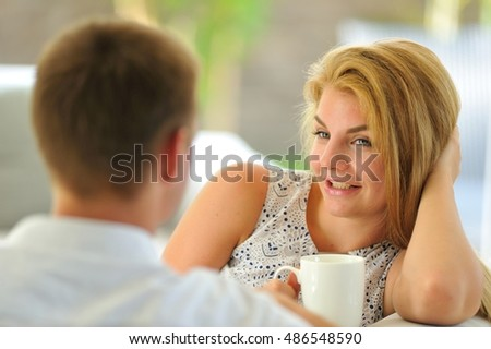Beautiful long-haired young blonde Russian lady sitting on a couch propped her head with one hand and holding a mug of delicious tea in another hand, chatting with husband
