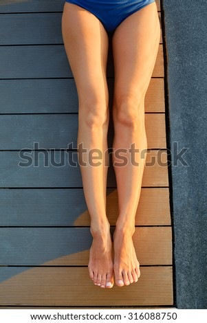 Beautiful long slender female legs sunbathing. Young woman with depilated, cellulite free, tanned legs relaxing outdoor and enjoying summer vacation . - stock photo