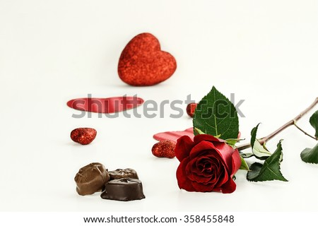 Beautiful long stem red rose with chocolate candy. Shallow depth of field. - stock photo
