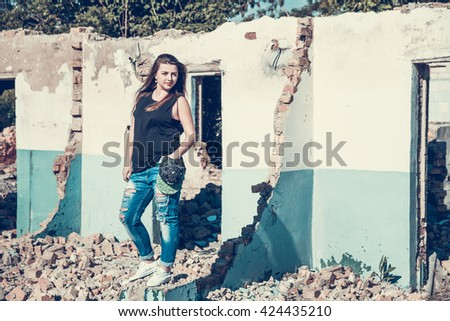 Beautiful, longhaired, dark-haired girl in cap, torn jeans and a black T-shirt on an abandoned house. Attractive woman in jean and cup outfit posing in old ruined factory house. tone photo - stock photo