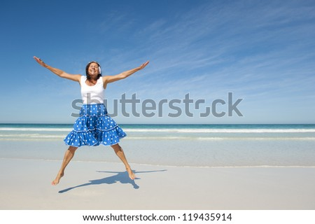 Beautiful looking and active senior woman enjoying retirement, jumping at beach, isolated with ocean and blue sky as background. - stock photo