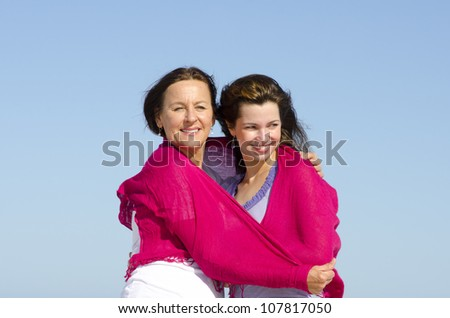 Beautiful looking couple of happy mother and daughter together outdoors at sunshine, with clear blue sky as background and copy space. - stock photo
