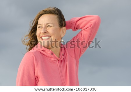 Beautiful looking happy mature woman, smiling and enjoying life, wearing purple sweater, isolated with dark cloud background and copy space. - stock photo