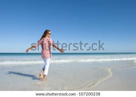 Beautiful looking mature woman, happy and friendly at beach, enjoying retirement, isolated with ocean and blue sky as background and copy space. - stock photo