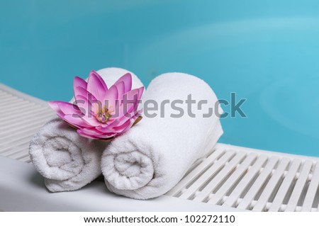 Beautiful lotus flower on towels at the edge of a pool at spa beauty club - stock photo