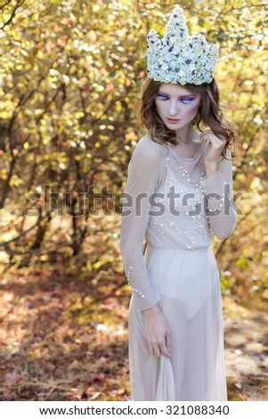 beautiful lovely gentle graceful fairy fairy in a flower crown and light dress walks through the woods on a sunny day early - stock photo