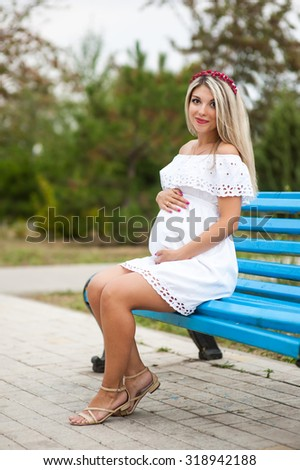 Beautiful lovely girl wearing her first child in the stomach and is looking forward to his birth. Strolling in the park, enjoy nature and quietness
