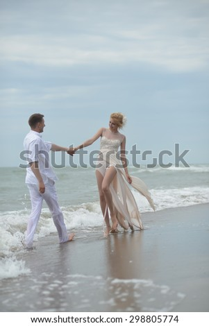 Beautiful lovely young wedding couple of man and woman in white standing holding hands on ocean beach shore on windy weather on blue sky background, vertical picture - stock photo
