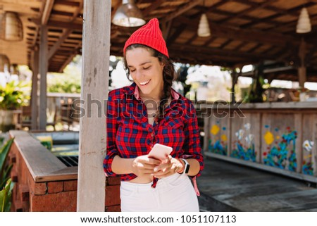 Superior Beautiful Lovely Young Woman With Dark Hair Dressed In Plaid Shirt And Red  Cap Poses With