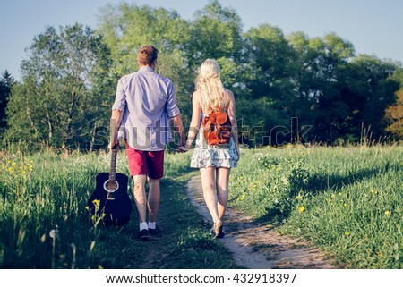 Beautiful loving couple going for a walk outdoors with guitar. Hippies