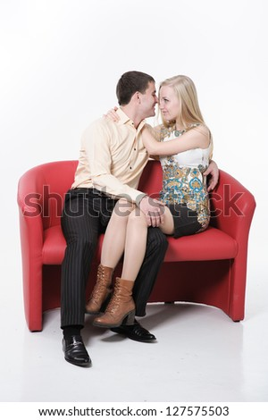 Beautiful loving couple hugging and having fun on red sofa. Happy Couple in Love