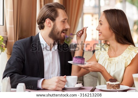 Beautiful loving couple is dating in restaurant. They are sitting at the table and smiling. The girl is feeding her boyfriend with sweet cake. The guy is eating it and drinking coffee - stock photo