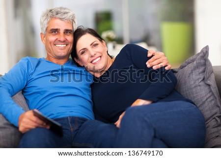 beautiful loving middle aged couple sitting on sofa - stock photo