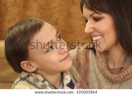 Beautiful luck Caucasian mama with her son on a brown background