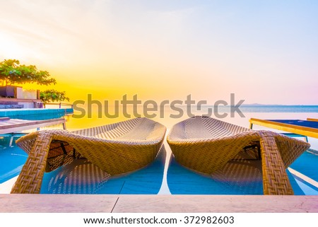 Beautiful luxury hotel swimming pool resort with umbrella and chair on the beach and sea - Vintage Filter and Boost up color Processing