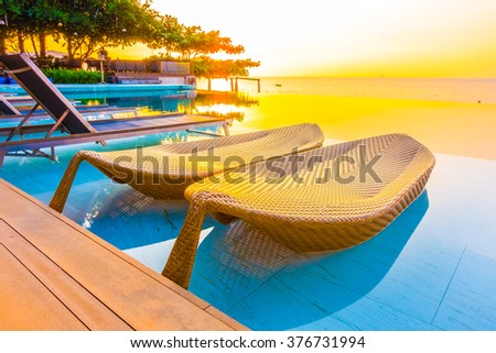 Beautiful luxury hotel swimming pool resort with umbrella and chair on the beach and sea - Vintage Filter and Boost up color Processing - stock photo