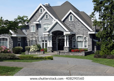 Beautiful luxury mansion with manicured front lawn. - stock photo