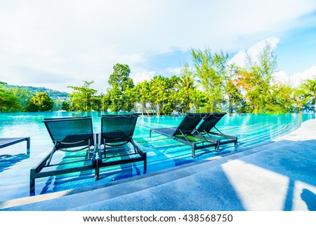 Beautiful luxury outdoor swimming pool in hotel resort with umbrella and chair on blue sky neary sea and ocean - Holiday vacation concept for background