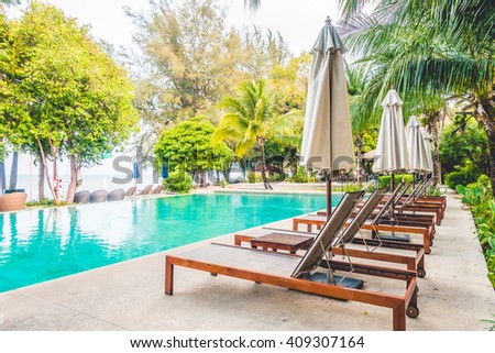 Beautiful luxury outdoor swimming pool with umbrella and chair around pool in hotel resort - Vintage light Filter