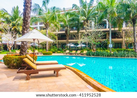 Beautiful luxury swimming pool with palm tree and sea background in hotel pool resort - Boost up color Processing