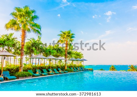 Beautiful luxury swimming pool with umbrella and chair in luxury hotel resort - Boost up color Processing style