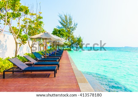 Beautiful luxury umbrella and chair around outdoor swimming pool in hotel resort neary sea and beach - stock photo