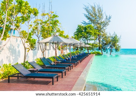 Beautiful luxury umbrella and chair around outdoor swimming pool in hotel resort neary sea and beach