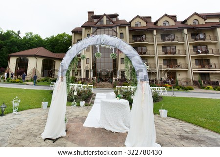 Beautiful luxury white wedding arc and venue with the hotel in the background - stock photo