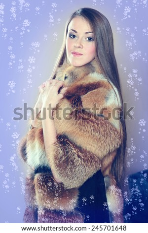 Beautiful luxury winter woman in fur coat. Brunette woman wearing a red fur coat. Coat of fox fur wearing a beautiful woman. Girl showing makeup on her face. Concept for advertising winter clothing.