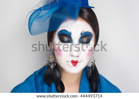 Beautiful magical charming oriental princess with a little blue hat, a grid on the head. Tie headdress. Figure white paint on her cheek blush, eye makeup, creative red heart on lips. Feather earrings - stock photo