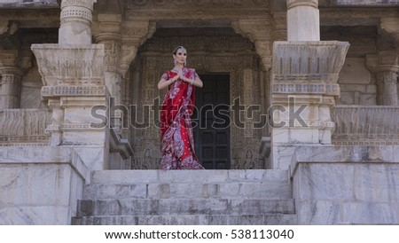 Beautiful Maharani. Young Indian Woman in Red bridal Sari clothing with bridal oriental jewelry. Beautiful Indian Girl in wedding Sari. Indian Bride in the ancient Temple. Wedding day