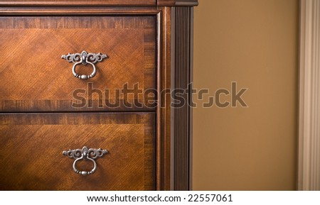 Beautiful mahogany wood cabinet. Detail shot with cream wall and molding in background. - stock photo