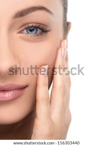 Beautiful make-up. Portrait of beautiful young women looking at camera touching her face - stock photo