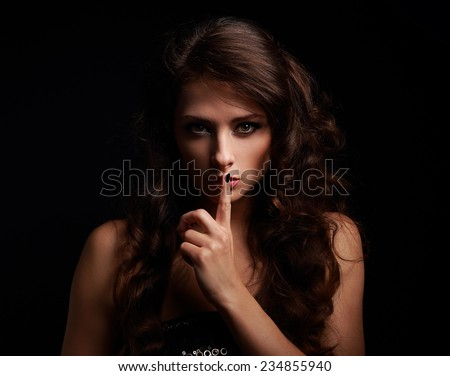 Beautiful make-up woman showing silence sign the finger near lips on black background - stock photo
