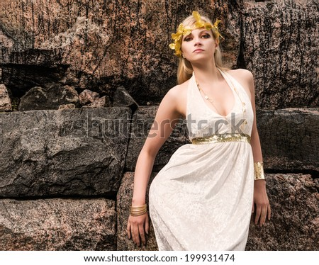 Beautiful makeup girl wearing white tunic and an antique jewels, rocky wall on background - stock photo