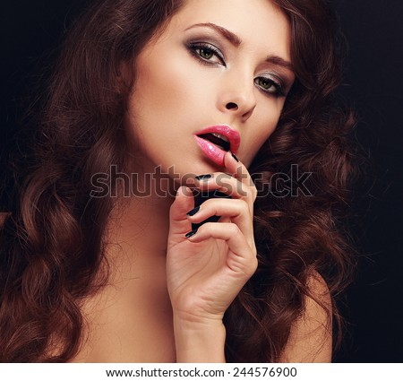 Beautiful makeup long hair woman looking sexy with finger near pink lips on black background. Closeup art portrait - stock photo