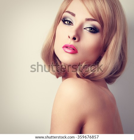 Beautiful makeup woman with green eyes and pink lipstick. Short hairstyle. Closeup toned portrait