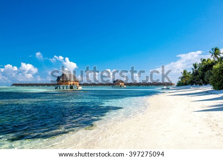 Beautiful Maldives beach with clear blue water and two honeymoon villas on background