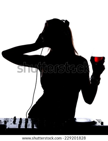 Beautiful male DJ with her headphones is standing at her deck mixing sound. - stock photo