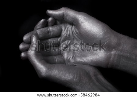 beautiful male hands in silver paint on black background