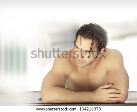 Beautiful male model in spa resort setting with lots of copy space - stock photo