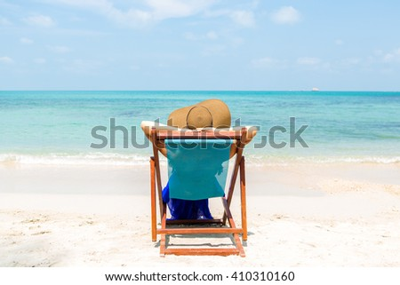 Beautiful mammy in long blue dress and beach straw hat relaxing in a beach chair. Cute woman relaxing and look to the sea shore. Lady near coastline. Photo from back. Happy mothers day. - stock photo