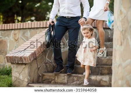 Beautiful man and child have a fun in the park together. A man dressed in a business-like style, using his free time to spend time with his lovely daughter. - stock photo