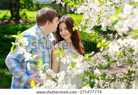Beautiful man and woman walking in the flowering spring park.
